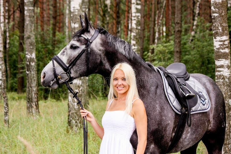 Piękna blondynki kobieta i szarość koń w lesie zdjęcia royalty free
