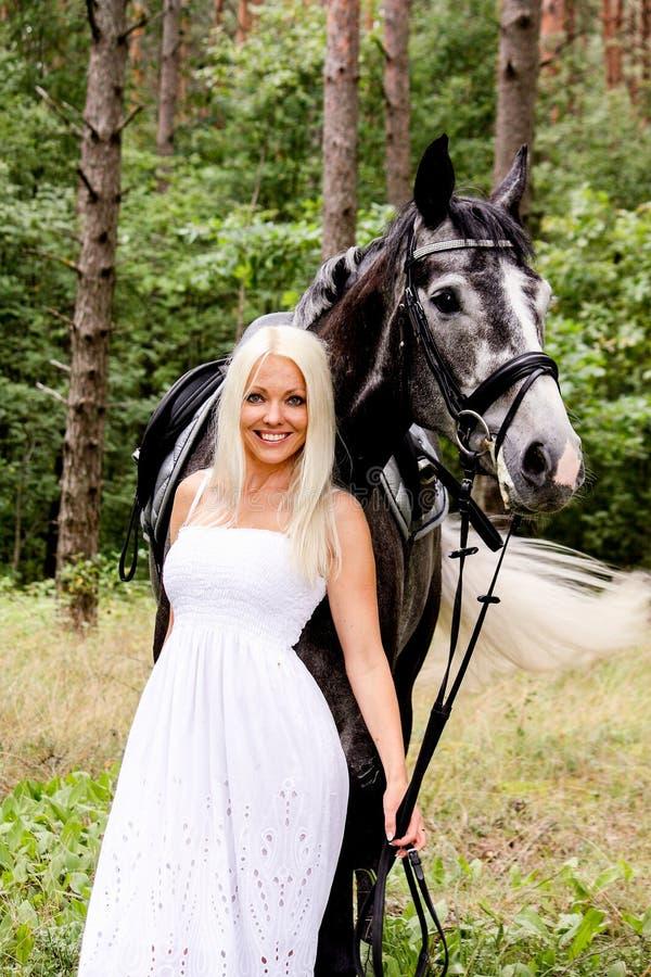 Piękna blondynki kobieta i szarość koń w lesie fotografia royalty free