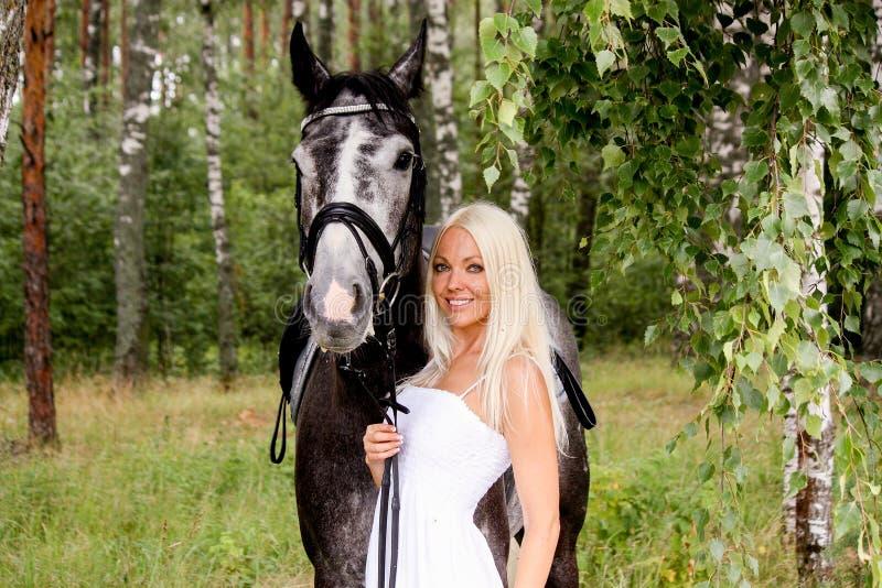 Piękna blondynki kobieta i szarość koń w lesie zdjęcie stock
