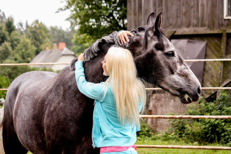 Piękna blondynki kobieta i szarość koń w lesie fotografia stock