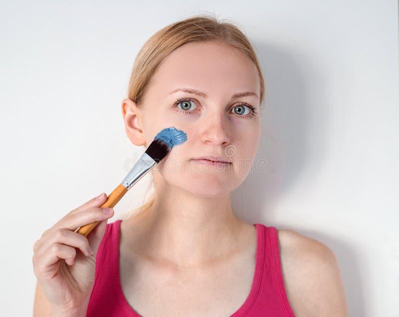 Piękna blondynki kobieta ma błękitną glinianą twarzową maskę stosuje beautician dziewczyna z maską na policzku jest uśmiechnięta obraz stock
