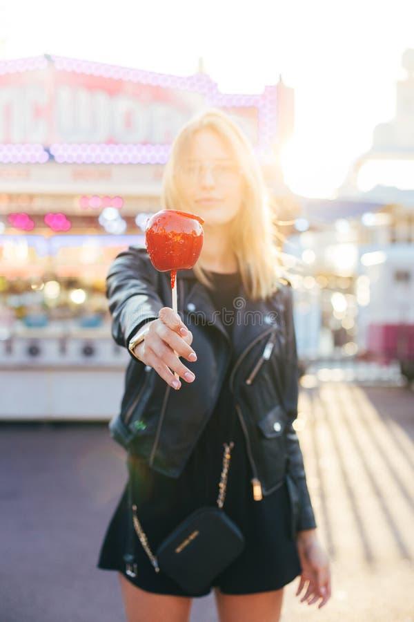 Piękna blondynki kobieta ono uśmiecha się z jabłczanym cukierkiem zdjęcie stock
