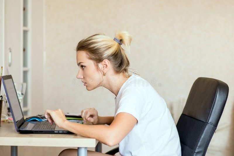 Piękna blondynki kobieta pracuje na laptopie w domu Jest rozważna i skupiająca się na pracie Freelance, pracuje w domu pojęcie zdjęcie stock