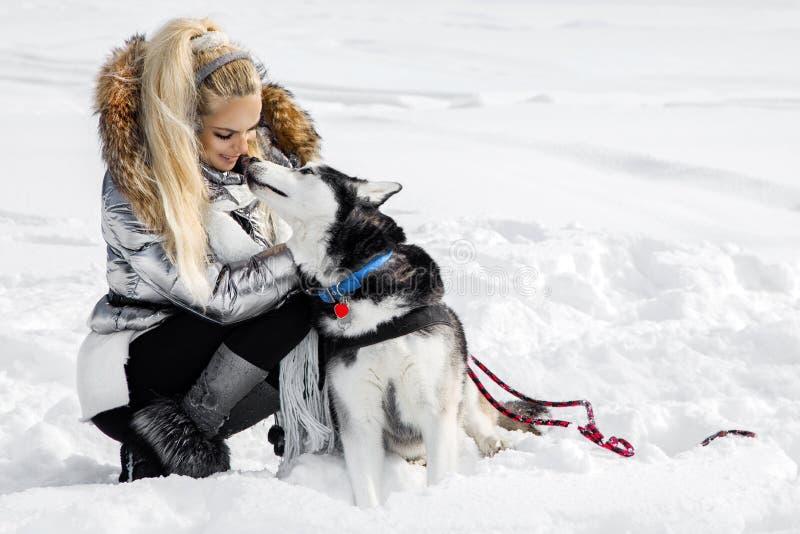 Piękna blondynki kobieta stoi na śniegu i trzyma Łuskowatego psa widok, góry i śnieg obraz royalty free