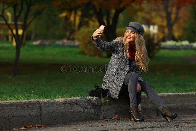 Piękna blondynki kobieta uśmiecha się selfie z smartphone i bierze obraz royalty free