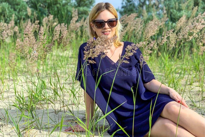 Piękna blondynki kobieta w błękit sukni pozuje okularach przeciwsłonecznych i podczas gdy siedzący na ziemi wśród trawy przy lato obrazy royalty free