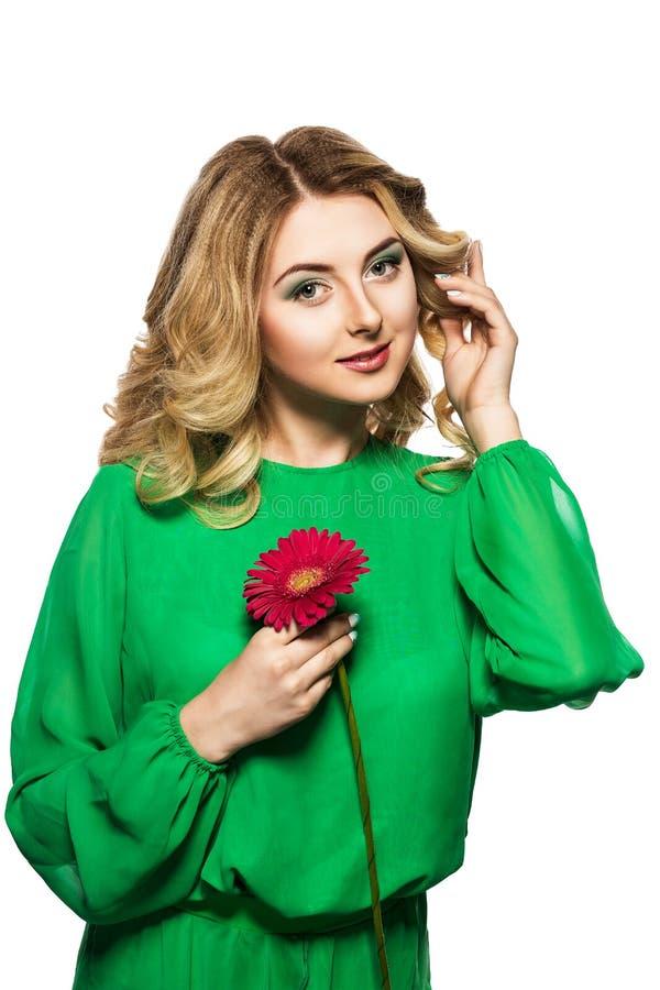 Piękna blondynki kobieta w zielonej sukni składał jej ręki blisko twarzy i koryguje fryzury mienia gerbera kwiatu zdjęcia royalty free