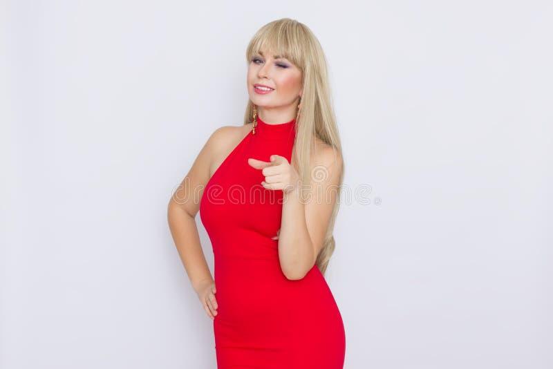 piękna blondynki kobieta z długie włosy w czerwonej wieczór sukni nad popielatym tłem Wearring na świętowaniu obraz royalty free