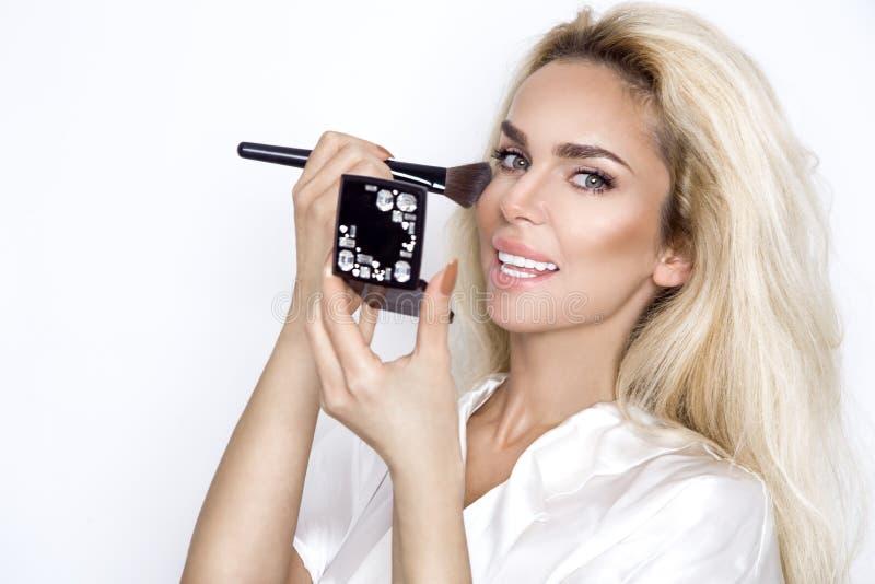 Piękna blondynki kobieta z perfect skórą, robi makeup obrazy royalty free