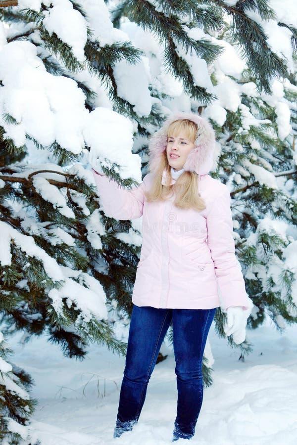 Piękna blondynki młoda kobieta jest ubranym różową kurtkę i niebieskich dżinsy obok śnieżnej sosny rozgałęzia się obrazy royalty free