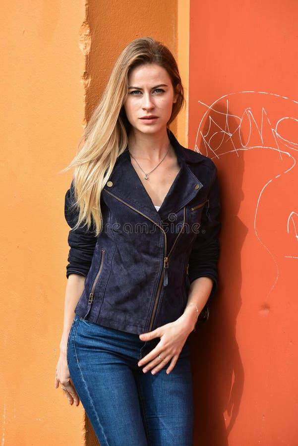 Piękna blondynki młoda kobieta pozuje blisko ściennego tła Uliczna moda fotografia stock