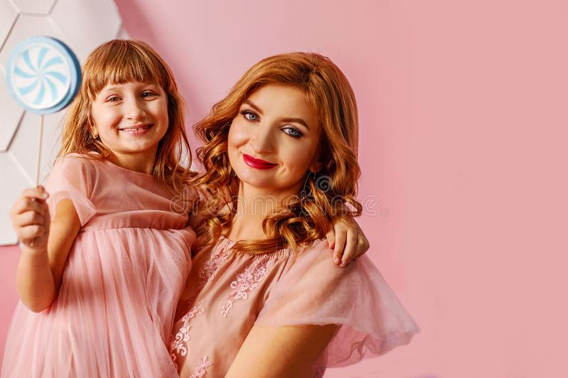 Piękna blondynki mama z śliczną córką w różowym tle w studiu Szczęśliwy matka dzień, córka ściska mamy i uśmiechu zdjęcie stock