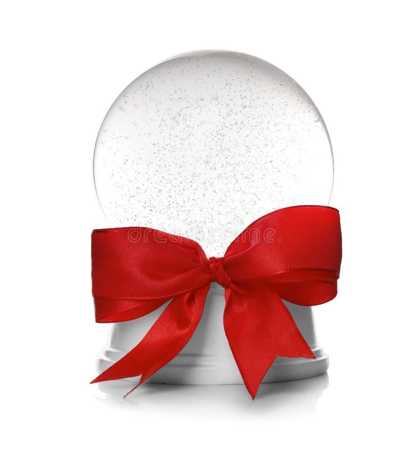 Piękna Bożenarodzeniowa śnieżna kula ziemska z czerwoną łęk kępką na bielu fotografia stock