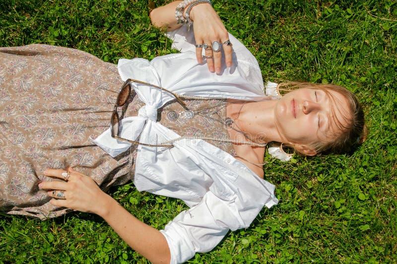 Pi?kna boho stylu kobieta z mn?stwo akcesoriami k?ama na trawie Szcz??liwy mometn i lata poj?cie fotografia stock