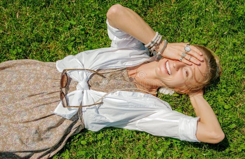 Pi?kna boho stylu kobieta z mn?stwo akcesoriami k?ama na zielonej trawie Szcz??liwy mometn obrazy royalty free