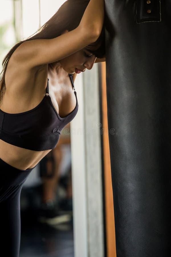 Piękna bokser młoda kobieta męczył brać przerwę od ćwiczenia opiera przeciw uderzać pięścią torbę w sprawności fizycznej gym Zdro zdjęcia royalty free