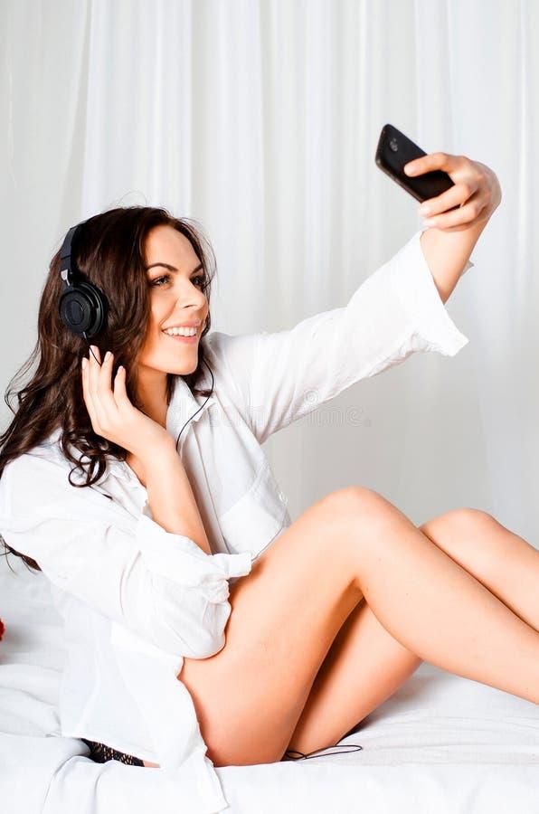 Piękna brązowowłosa dziewczyna w biały koszula i skrótów siedzieć fotografia stock