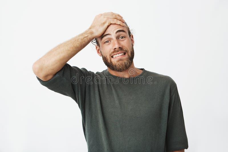 Piękna brodata mężczyzna mienia ręka na czole z przelękłym wyrażeniem zapominał że jego żona pytał on robi czyścić up zdjęcia royalty free