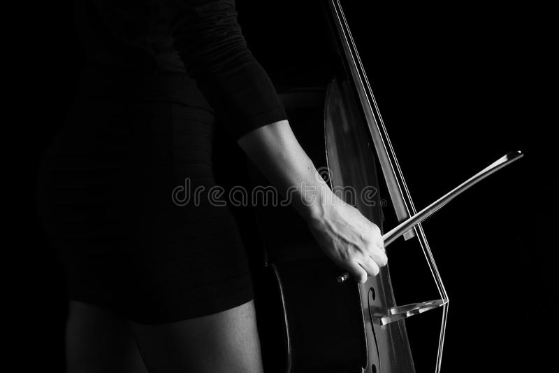 Piękna brunetka bawić się wiolonczelę z selekcyjnym światłem w czarnym d obrazy stock