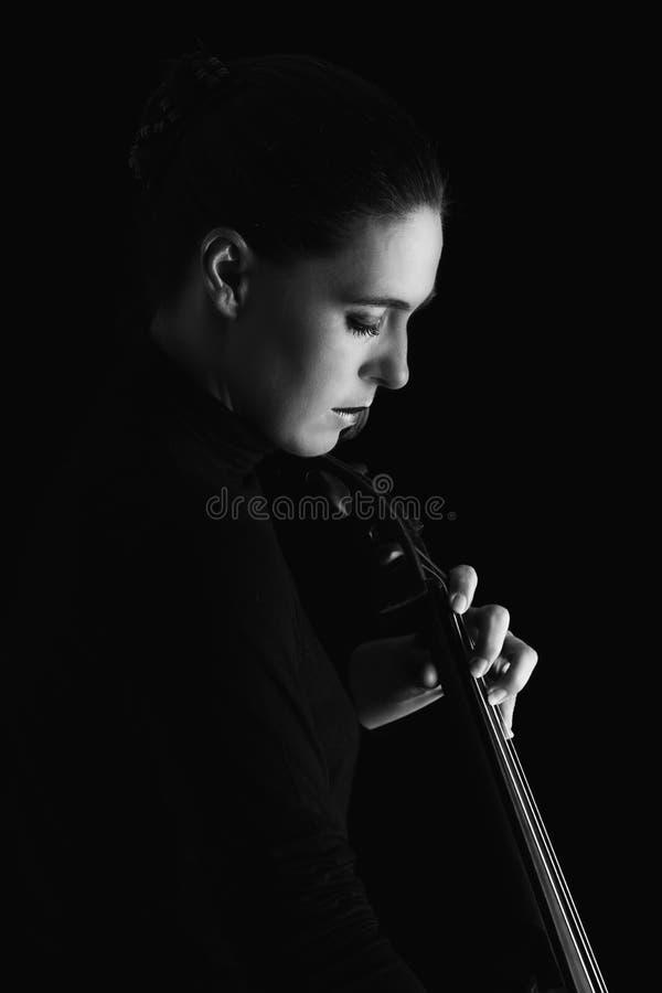 Piękna brunetka bawić się wiolonczelę z selekcyjnym światłem w czarnym d zdjęcie royalty free
