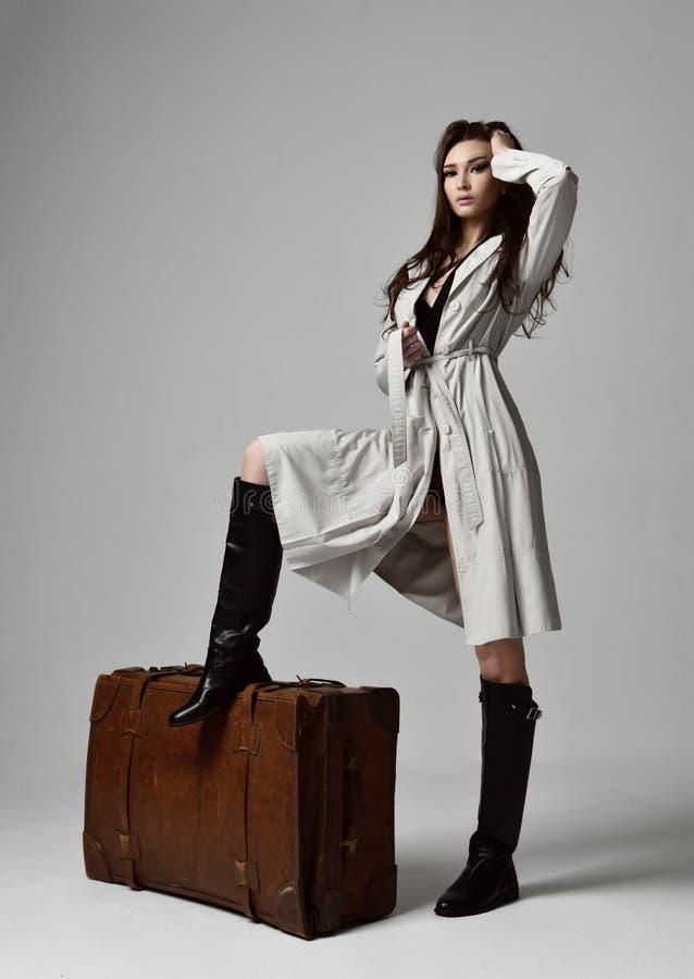 Piękna brunetka modnisia kobieta w szarej jesieni kurtce z wietrzną włosianą siedzącą pobliską rzemienną brown retro podróży torb obrazy stock