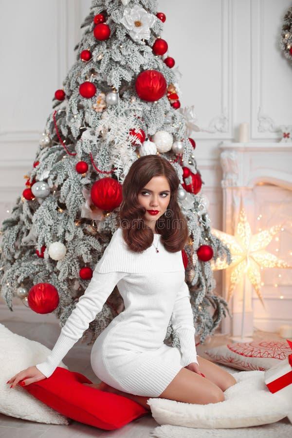 Piękna brunetka w Bożenarodzeniowym wnętrzu Elegancka zimy kobieta w biel sukni teraźniejszości prezenta pudełku z czerwonym tasi zdjęcia stock