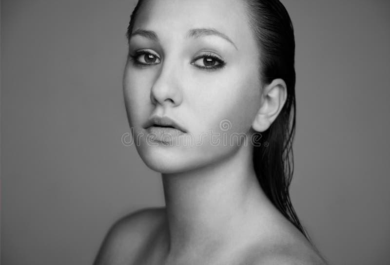 Piękna brunetka w pięknie strzelał portret z mokry włosiany patrzeć w kamerze. Biała fotografia. fotografia royalty free