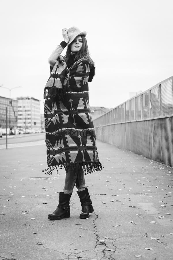 Piękna brunetka z kapeluszem pozuje w ulicie obraz stock