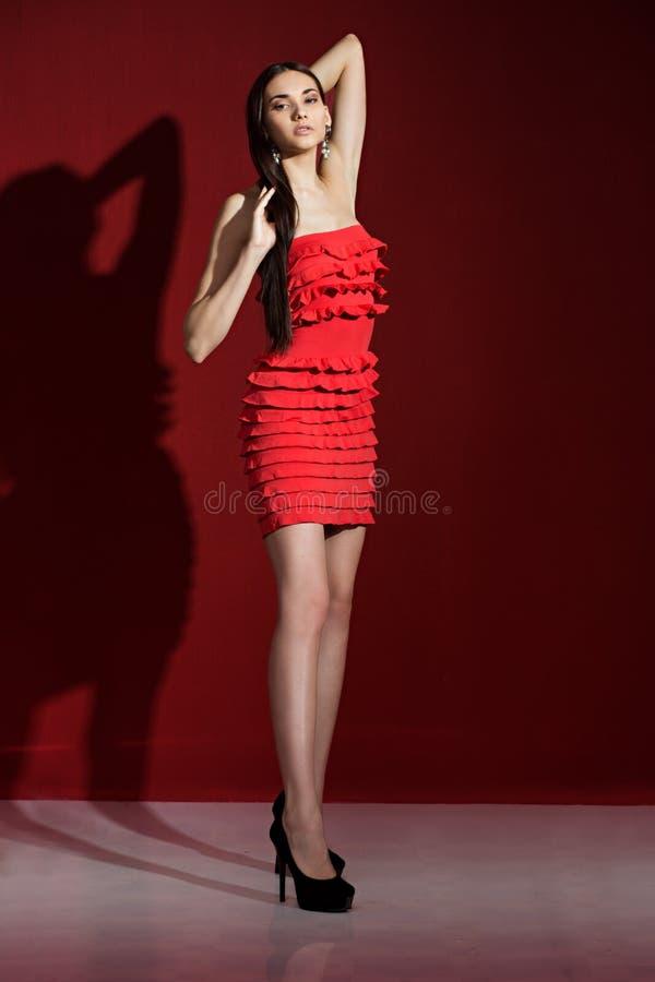 Piękna brunetka z wewnątrz czerwoną suknią zdjęcie stock