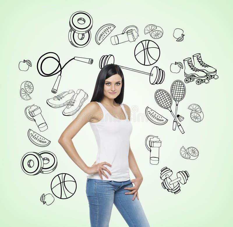 Piękna brunetki dama która próbuje robić wyborowi na rzecz pewnej sport aktywności Sport ikony rysują na świetle zdjęcia royalty free