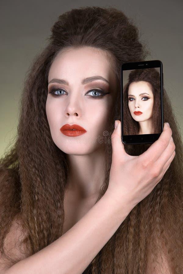 Piękna brunetki dziewczyna i jej selfie na telefonie obraz royalty free