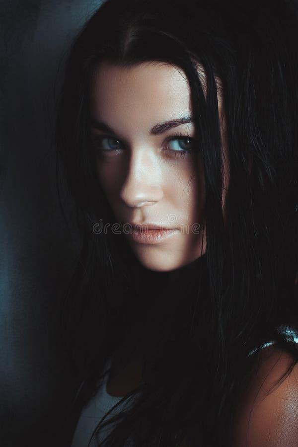 Piękna brunetki dziewczyna nad ciemności tłem obraz stock