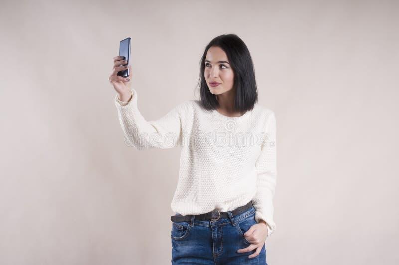 Piękna brunetki dziewczyna robi selfie studiu pozuje szczęście puloweru cajgi obrazy stock