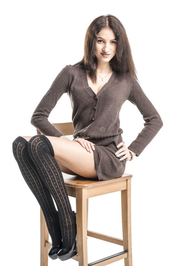 Piękna brunetki dziewczyna w czarnych pończoch rozochoconych uśmiechach Hamming fotografia stock