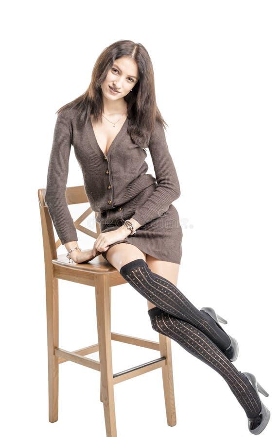 Piękna brunetki dziewczyna w czarnych pończoch rozochoconych uśmiechach Hamming obraz stock