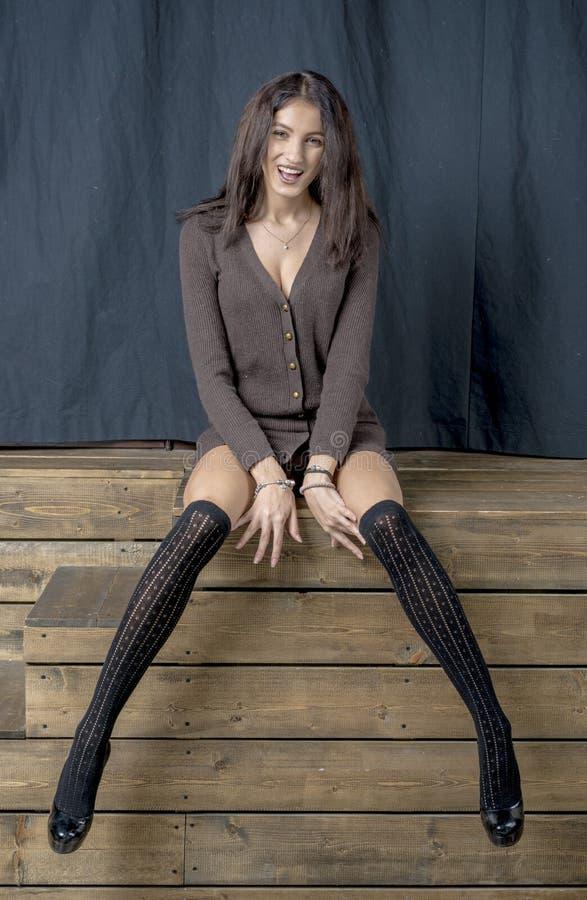 Piękna brunetki dziewczyna w czarnych pończoch rozochoconych uśmiechach Hamming obraz royalty free