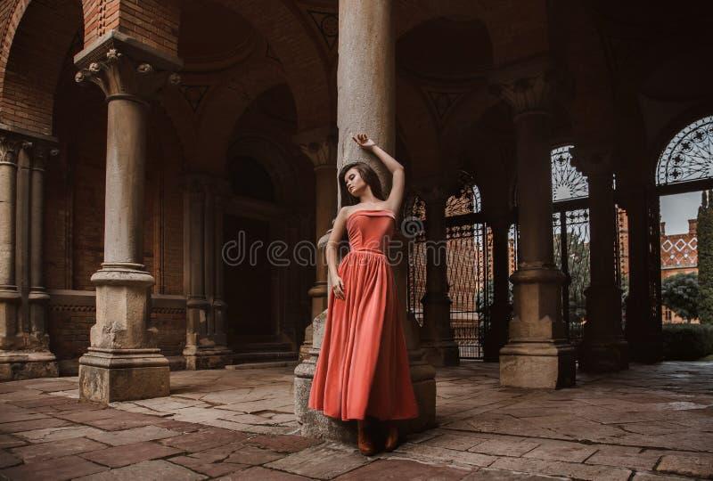 Piękna brunetki dziewczyna z bardzo długie włosy, w pomarańcze, rocznik suknia zdjęcie royalty free