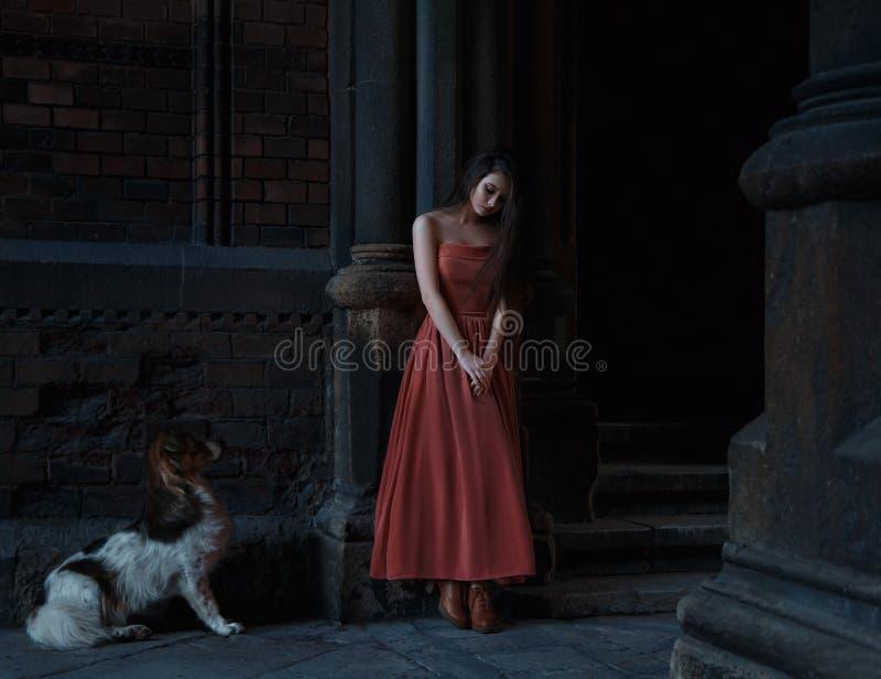 Piękna brunetki dziewczyna z bardzo długie włosy, w pomarańcze, rocznik suknia zdjęcie stock