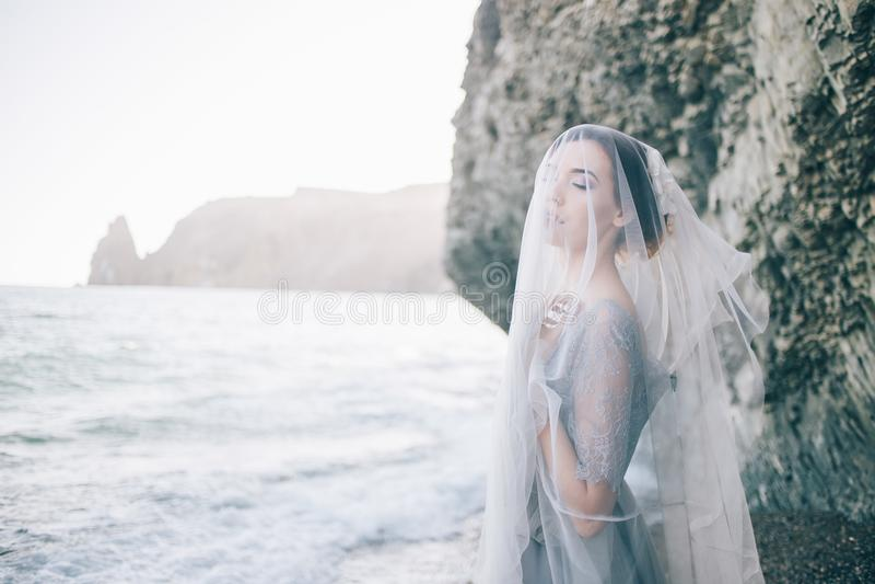 Piękna brunetki dziewczyny panna młoda w popielatej todze koronka i tiul, zakrywającej jej twarz z przesłoną, ręka na piersi, fotografia stock