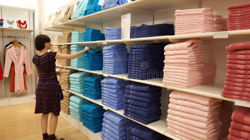 Piękna brunetki kobieta egzamininuje ręczniki w sklepie w Eskisehir zdjęcie stock