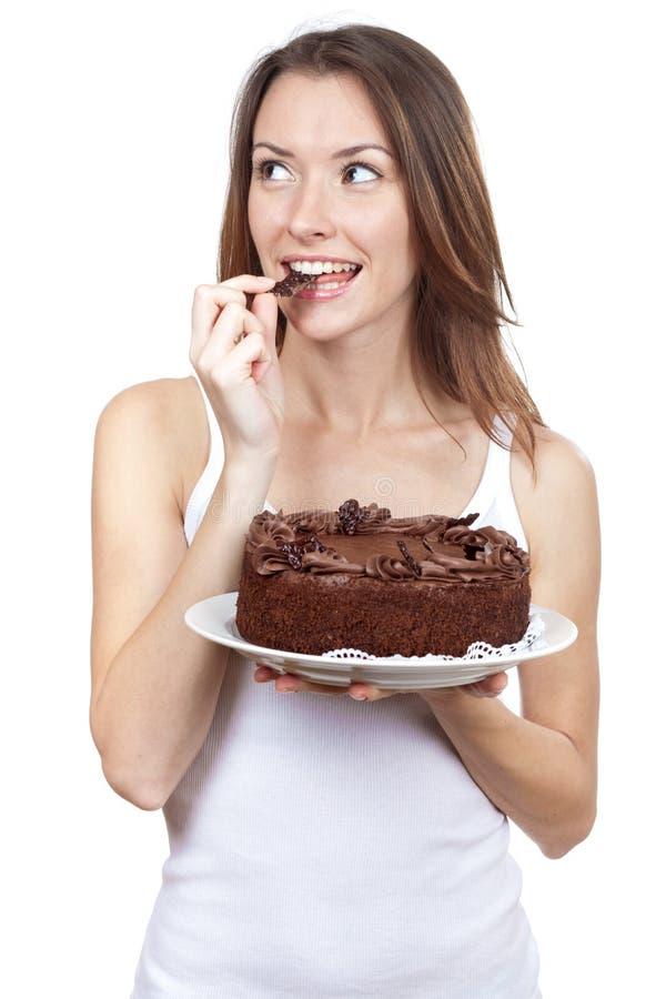 Piękna brunetki kobieta je czekoladowego tort zdjęcie royalty free
