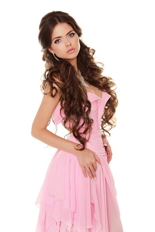 Piękna brunetki kobieta jest ubranym w menchii sukni odizolowywającej na bielu zdjęcia stock