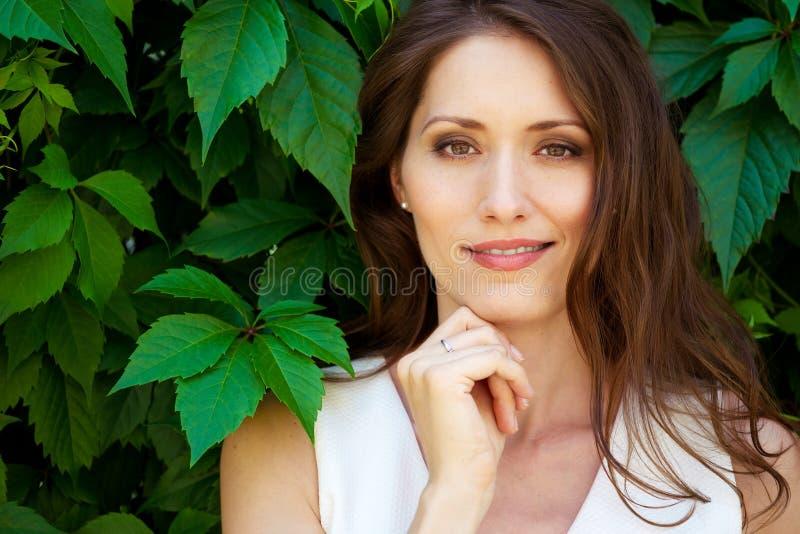 Piękna brunetki kobieta outdoors z zielonym środowiskiem obrazy royalty free