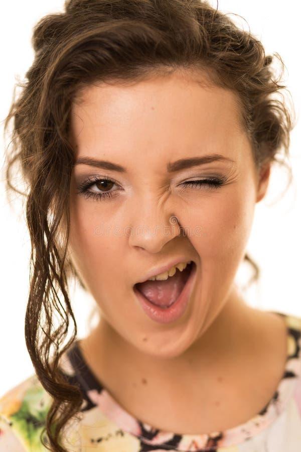 Piękna brunetki kobieta Robi Śmiesznemu mrugnięciu fotografia stock