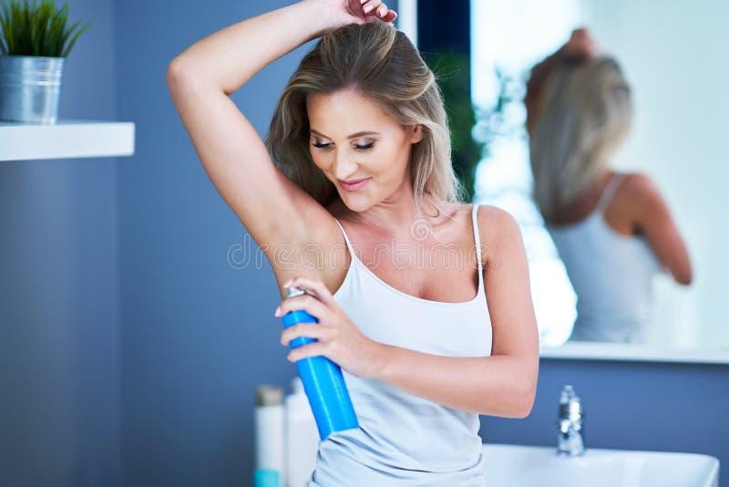 Piękna brunetki kobieta używa dezodorant w łazience fotografia stock