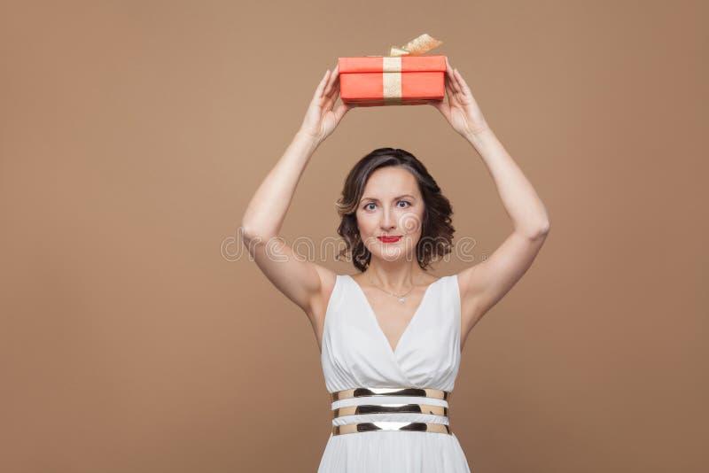Piękna brunetki kobieta w biel sukni mienia prezenta czerwonym pudełku wewnątrz obraz stock