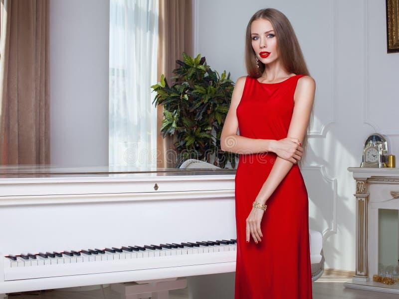 Piękna brunetki kobieta w czerwonej sukni piękny taniec para strzału kobiety pracowniani young długie włosy czerwone usta fotografia royalty free