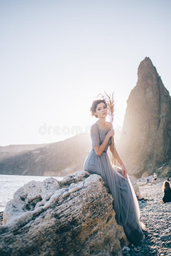 Piękna brunetki kobieta w długim smokingowym siedzącym bielu kamieniu morzem przy zmierzchem i patrzeć kamerę zdjęcie stock