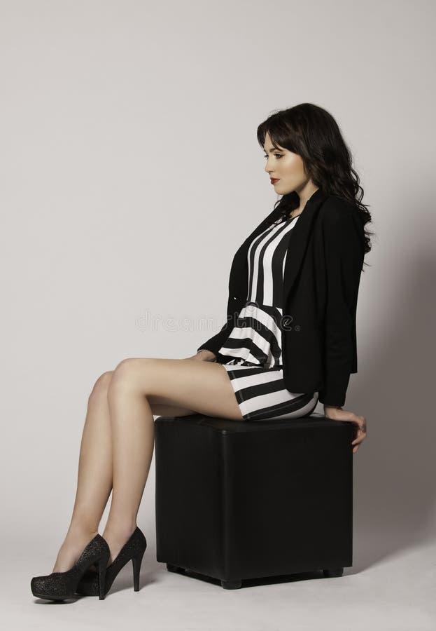Piękna brunetki kobieta w tylnym i białym garnituru obsiadaniu na leżance zdjęcia royalty free