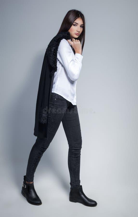 Piękna brunetki kobieta z uroczy długie włosy pozować w białej koszula i cajgach w studiu bedsheet moda kłaść fotografii uwodzici zdjęcia stock
